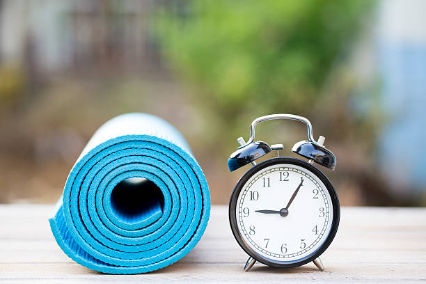 time for exercising clock and yoga mat, outdoor - trainer uhr stock-fotos und bilder