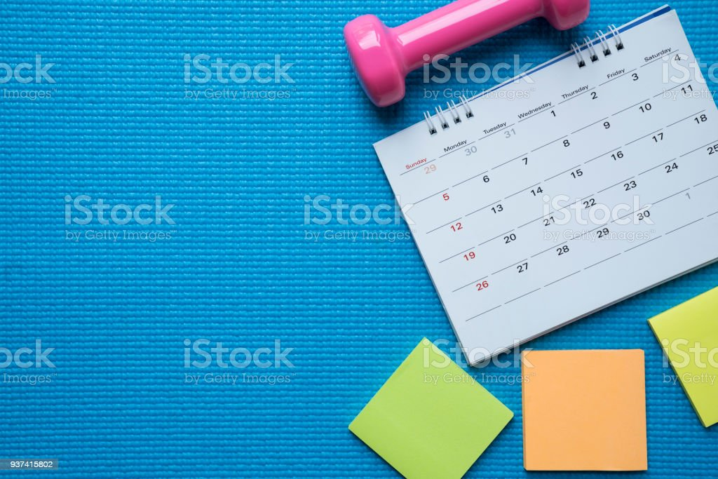 Time for exercising clock, calendar and dumbbell with blue yoga mat background stock photo