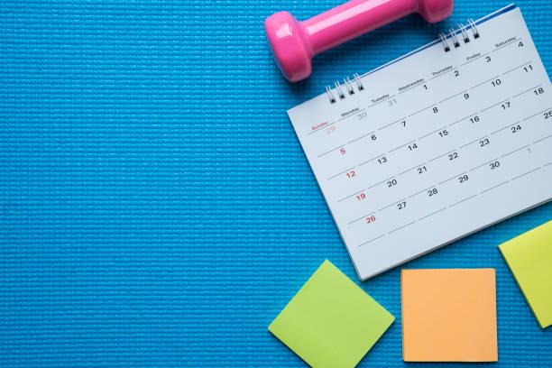 tid för att utöva klocka, kalender och hantel med blå yoga matta bakgrund - calendar workout bildbanksfoton och bilder