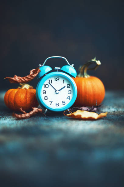 Time for Fall. Alarm clock with leaves and pumpkins. Daylight Savings Time. stock photo