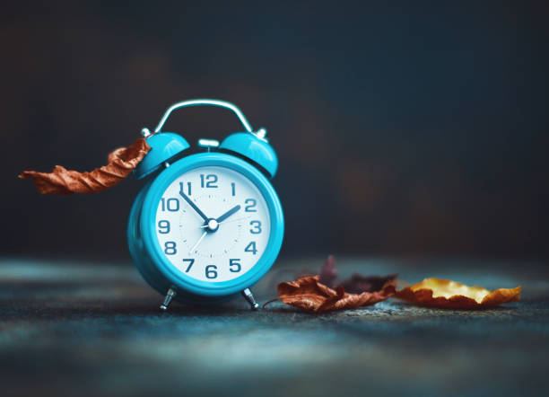 Time for Fall. Alarm clock with leaves. Daylight Savings Time. stock photo