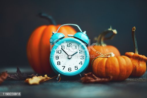 Time for Fall. Teal alarm clock with leaves and Pumpkins