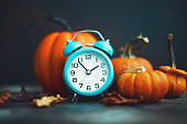 istock Time for Fall. Teal alarm clock with leaves and Pumpkins 1193220915