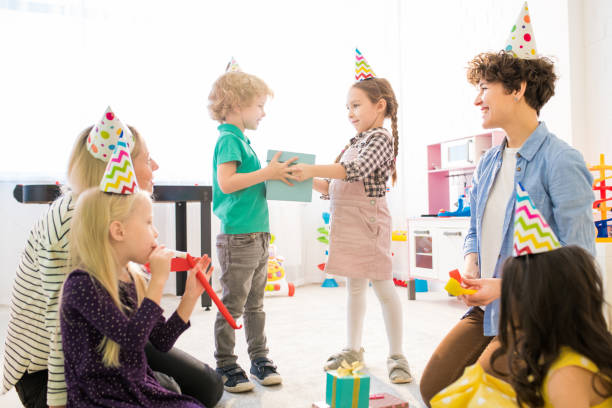 Time for gifts at birthday party Time for gifts at birthday party: positive cute girl with braids and giving gift box to curly-haired boy while congratulating him with birthday at party group of friends giving gifts to the birthday girl stock pictures, royalty-free photos & images