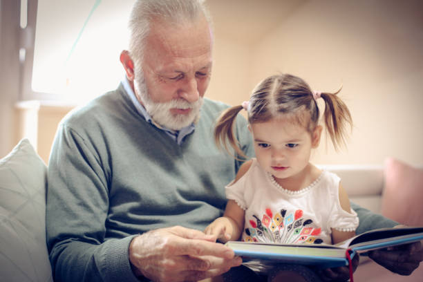 Time for grandchild. Happy grandfather and granddaughter reading book together at home. Close up. granddaughter stock pictures, royalty-free photos & images