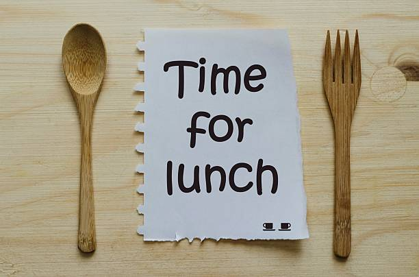 Time for lunch written on note between spoon and fork Time for lunch written on note between spoon and fork over wooden background between stock pictures, royalty-free photos & images