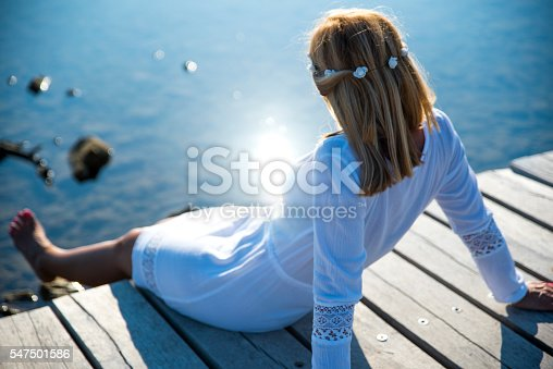 Adult blond woman sitting on a wooden dock by the sea and enjoying the sun reflecting in the water. She is wearing hair accessorie made of flowers.