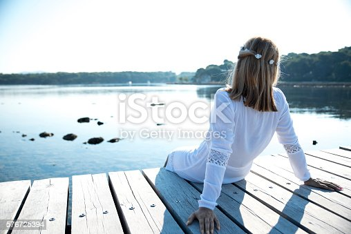 Young blond woman in a white dress sitting on a wooden dock and looking at a beautiful sea. View from the back.