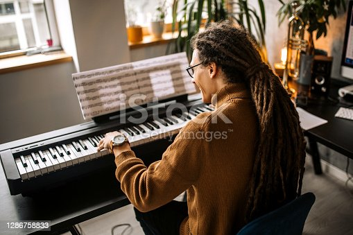 Young handsome musician playing his digital piano in his home recording studio