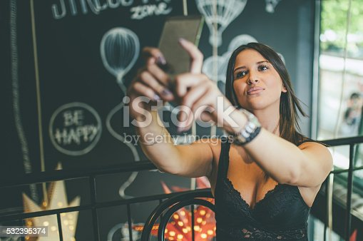 young attractive woman doing selfie with smartphone at coffee shop