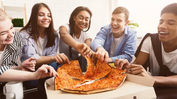 hora de la merienda. estudiantes felices comiendo pizza y charlando - ocio fotografías e imágenes de stock