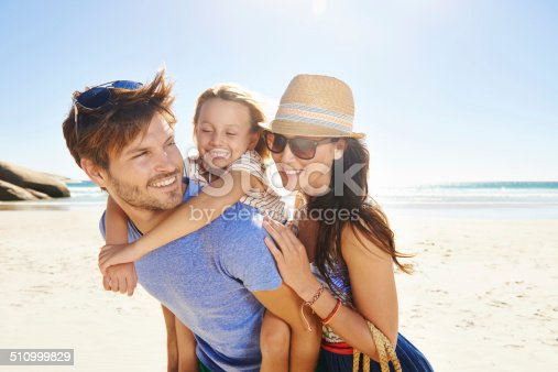 Cropped shot of a young one child family on a beach with the father giving his daughter a piggyback