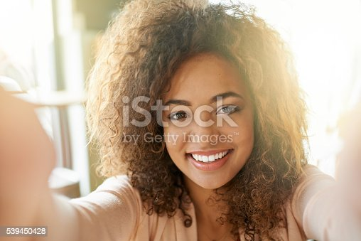 Portrait of a smiling young woman taking a selfie in a cafe