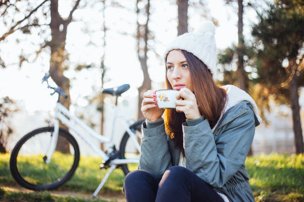Time for some tea Women resting after riding bicycle in park. She is drinking hot drink and enjoy in beautiful autumn day. female biker resting stock pictures, royalty-free photos & images
