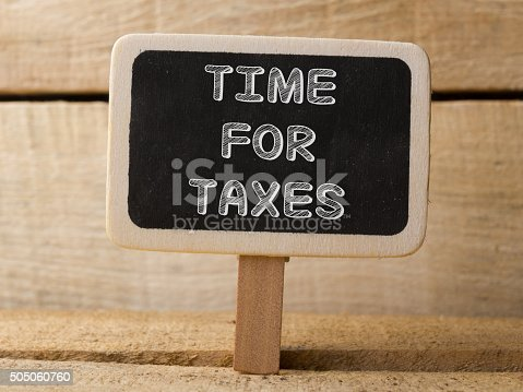 Chalkboard on wooden background with Time For Taxes words