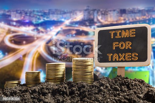 Time for Taxes - Financial opportunity concept. Golden coins in soil Chalkboard on blurred urban background.