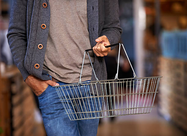 Time for this week's shopping Cropped shot of a young man carrying a shopping basket and walking in a grocery store shopping basket stock pictures, royalty-free photos & images
