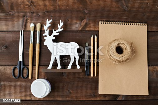 Art & craft equipment and reindeer statuette on wooden table
