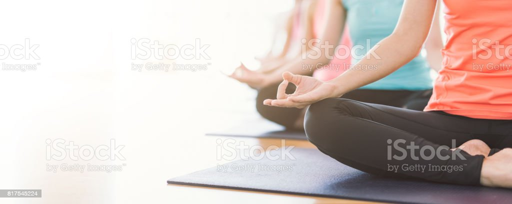 Time for yoga. Attractive young Asian woman group exercising and sitting in yoga lotus position in yoga classes stock photo