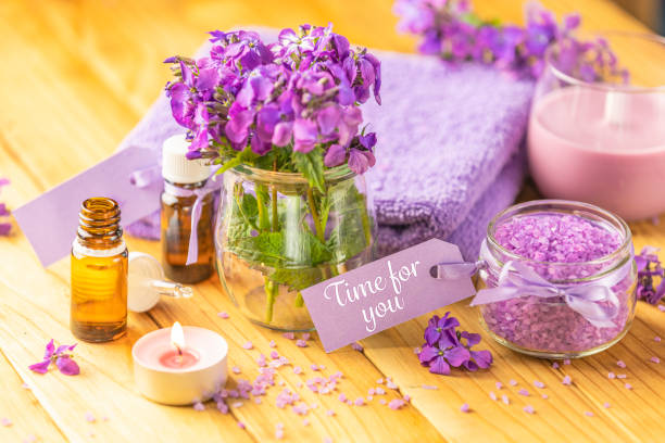Time for you text phrase on label sticker. Spa still life with violet oil, towel, violaceous bath salt in glass jar and perfumed candle on natural wood table surface stock photo