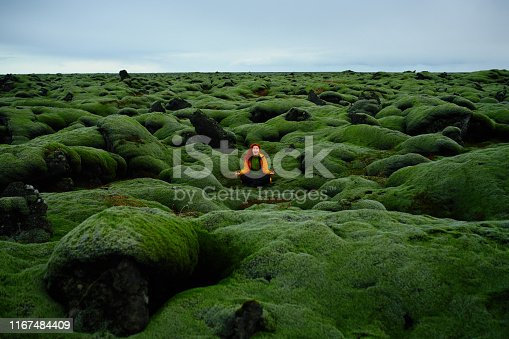 Red-haired hiker woman in nature enjoying the day in Iceland, sitting on hill covered in moss