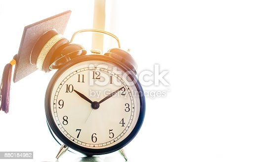 959387240 istock photo Time is  Education, Graduation cap on top clockConcept of educational times Studies lead to success in life, Graduate study abroad program. 880184982