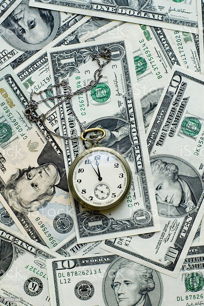 Time is money- clock and dollars stock photo