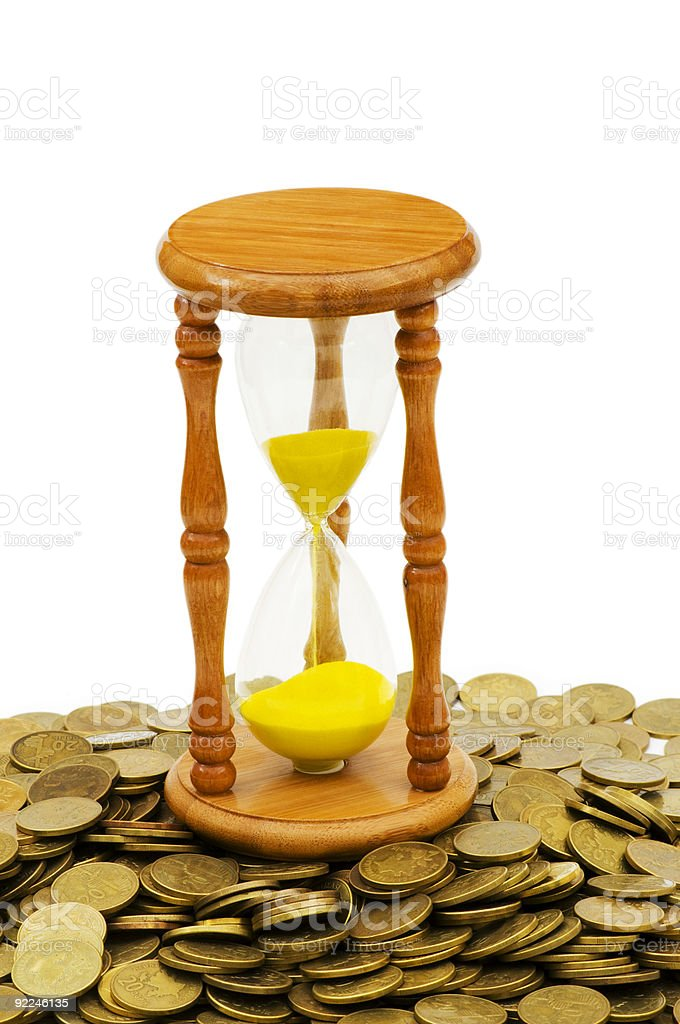 Time is money concept - hourglass and coins royalty-free stock photo