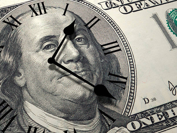 Time is money concept Time is money concept with one hundred dollars note and clock face on it. time is money stock pictures, royalty-free photos & images