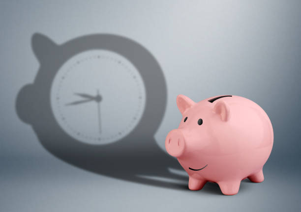 time is money concept, piggy bank with clock shadow on grey stock photo