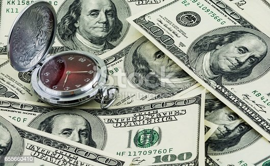 Time is money concept, traditional pocket watch and one hundred US dollar banknotes