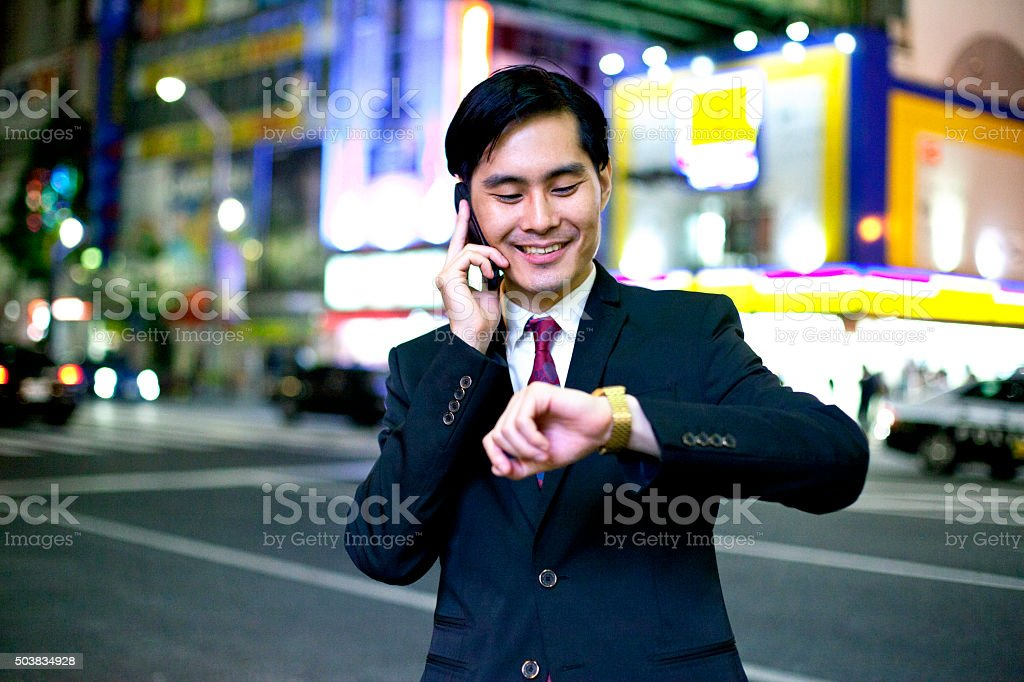 Time is money - japanese businessman at night in Tokyo, Japan....