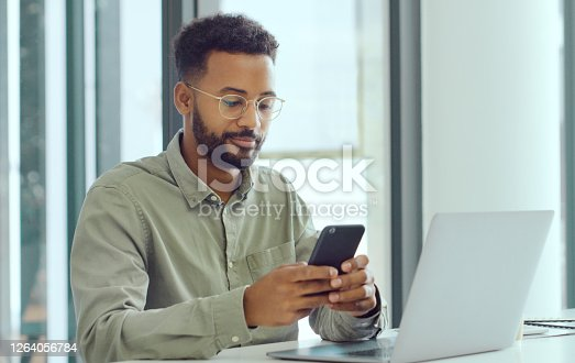 Shot of a young businessman using a smartphone and laptop in a modern office