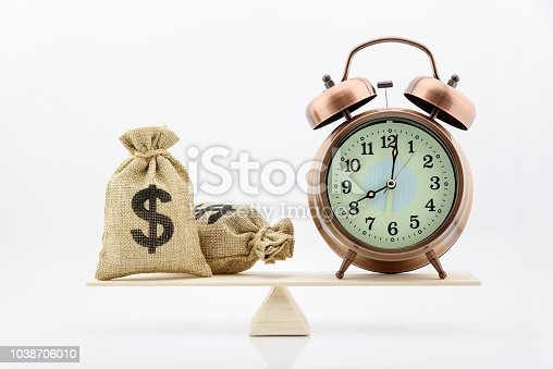 istock Time is money or time saving concept : Dollar or cash in hessian bags / burlap sacks and vintage clock on wood balance scale, depicts the importance of time and money that everyone should balance well 1038706010