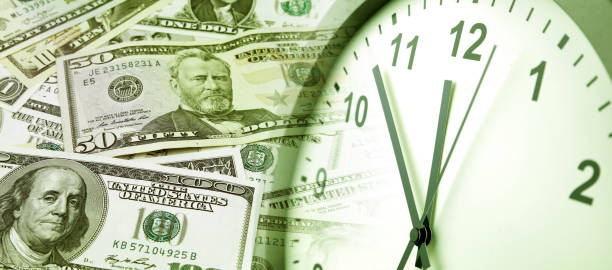 Time is money Clock and assorted American banknotes. Time is money idea time is money stock pictures, royalty-free photos & images