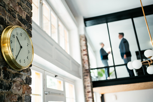 Low view of a two confident business persons at a meeting, seen through glass wall in the office. Businessman and businesswoman in meeting discussing business strategy. Business colleagues working together in the office. The view is through glass. Focus is on the clock on the wall.