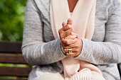 Closeup shot of an unrecognizable woman holding her hands together outdoors