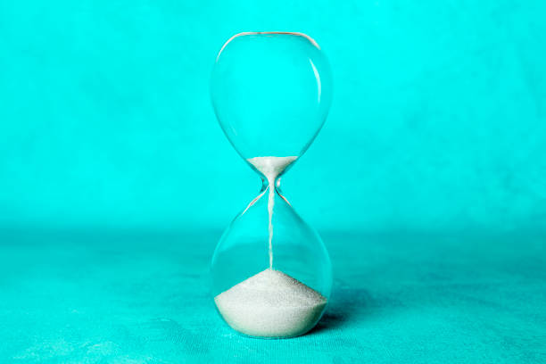 time is running out concept. an hourglass with sand falling through, on a vibrant blue background with a place for text - perdita di peso foto e immagini stock