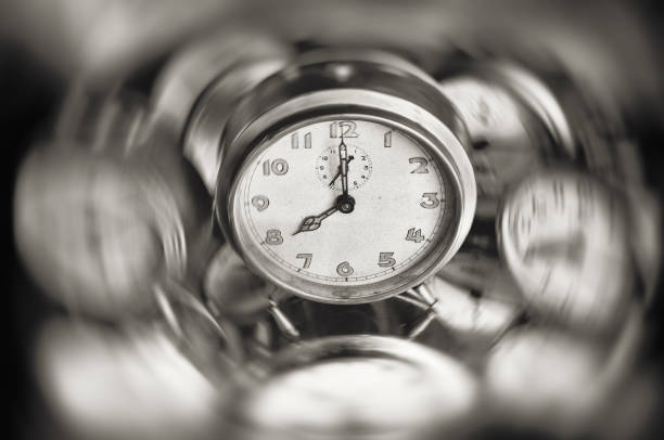 Time is spinning fast, concept image with clock. Vintage alarm clock in the middle of spinning motion blur, textured in black and white. ASAP stock pictures, royalty-free photos & images