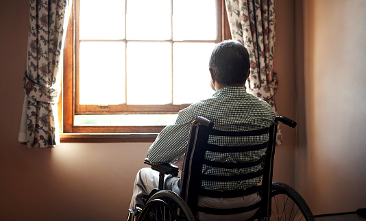 Rearview shot of a senior man looking out the window while sitting in his wheelchair