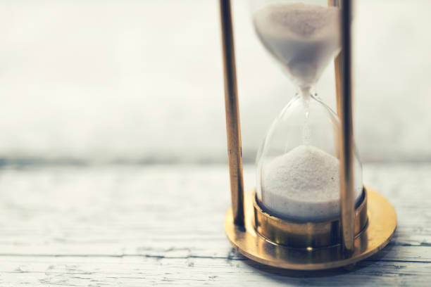 time is ticking - hourglass on the table with copy space time is ticking - hourglass on the table with copy space patience stock pictures, royalty-free photos & images