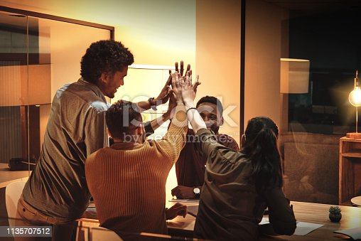 Shot of a group of businesspeople giving each other a high five in an office at night