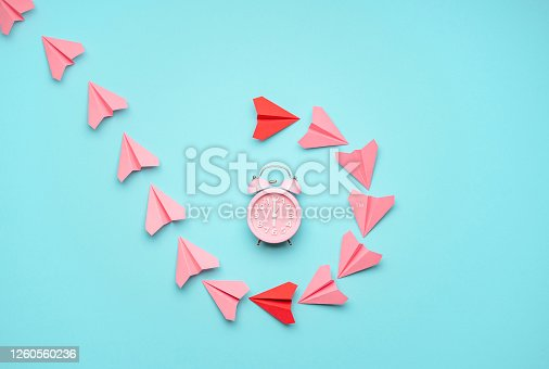 Flat lay with pink and red paper airplanes around a pink clock on a blue background. Time flies concept with paper planes flying around the alarm clock
