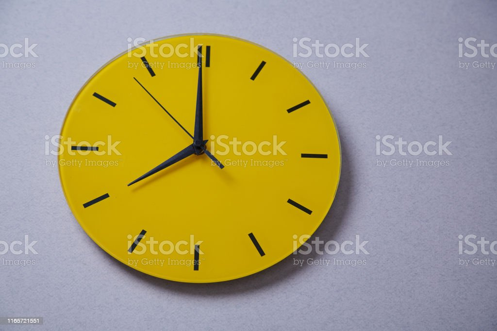 Time management deadline and schedule concept: yellow clock. Close up.