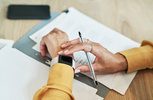 Closeup shot of an unrecognisable businesswoman checking her wristwatch while writing notes in an office