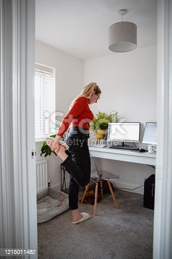 Young Caucasian female taking time out to stretch whilst  working from her home office.