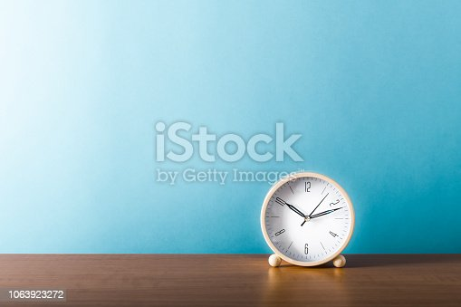 Desk clock on office wooden desk table. With copy space. Shot with ISO64.