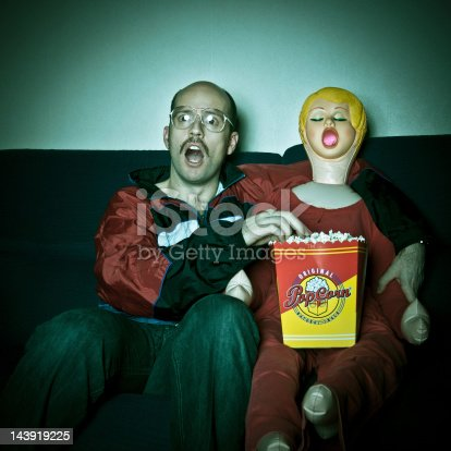 Nerdy looking guy and blow up doll watching TV