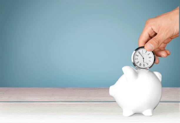 Time. Hand depositing  clock  in piggy bank on background time is money stock pictures, royalty-free photos & images