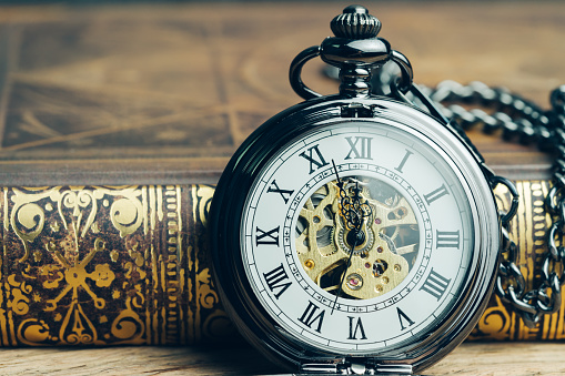 Time running, deadline, life time or business milestone concept, closed up vintage pocket watch or clock on book in vintage tone